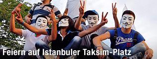 Jugendliche mit Guy-Fawkes-Masken zeigen Victory-Zeichen