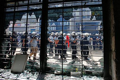Polizisten vor dem zerstörten Fenster einer Bank