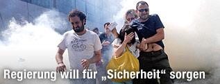 Personen gehen durch Tränengasschwaden