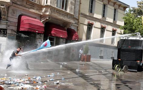 Demonstrant mit Fahne wird von einem Wasserwerfer getroffen