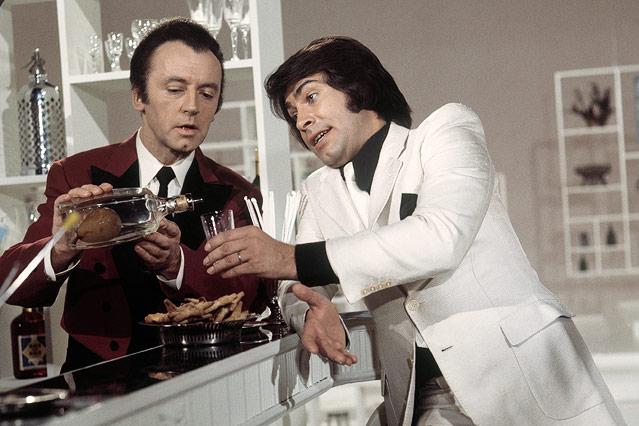Eddi Arent schenkt dem Sänger und Schauspieler Roy Black ein Glas ein