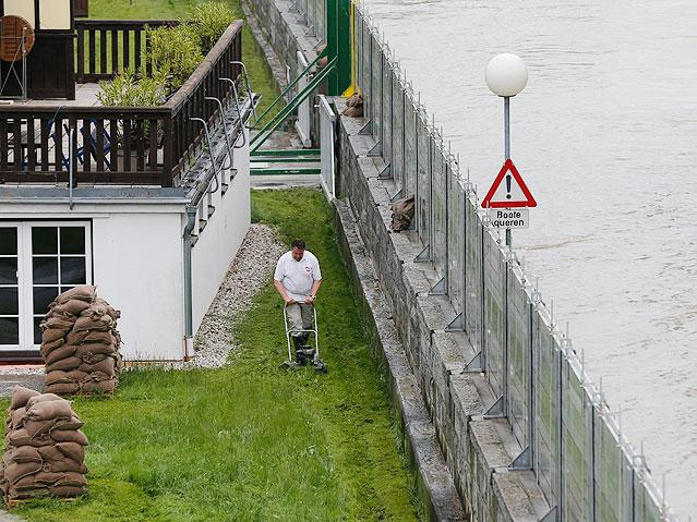 Mann mährt den Rasen hinter einem Hochwasserschutzdamm