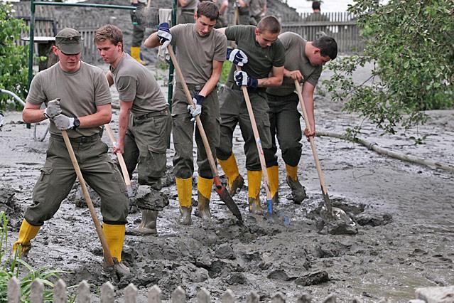 Soldaten schaufeln Schlamm