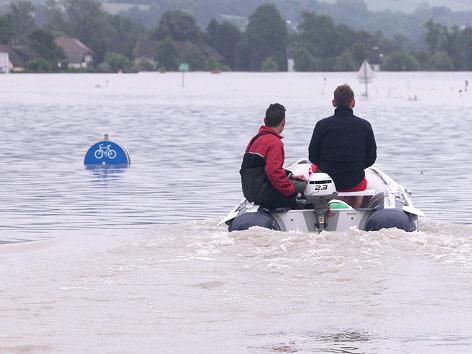 Motorboot und überflutete Verkehrszeichen