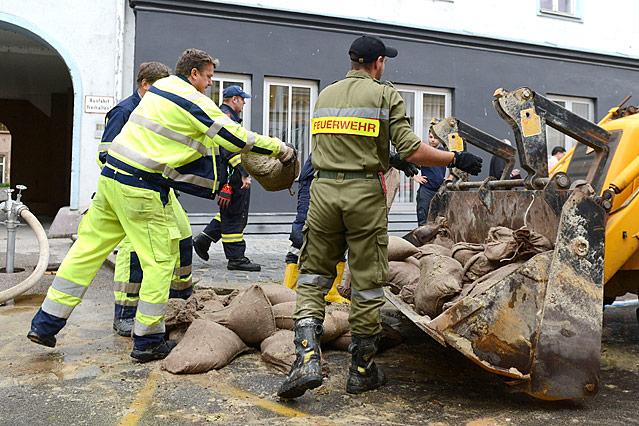 Feuerwehrmänner werfen Sandsäcke in Baggerschaufel