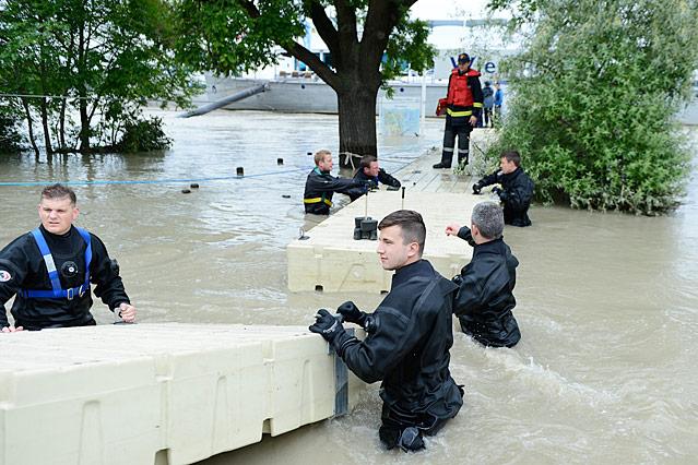 Feuerwehrleute beim Bau eines Versorgungssteges zu einem Schiff auf der Donau