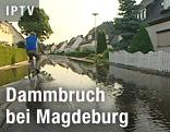 Mann fährt mit Fahrrad auf überschwemmter Straße