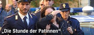 Frau wird von Polizei abgeführt