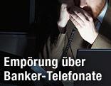 Banker hält sich beim Telefonieren die Hand vor den Mund