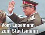 Belgiens König Albert II. sitzt in einem Auto und winkt