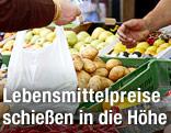 Frau kauft auf einem Markt Erdäpfel