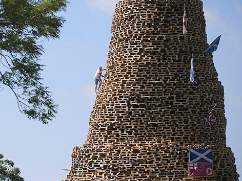 Mann klettert auf Turm aus Paletten