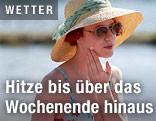 Frau cremt sich mit Sonnenmilch ein