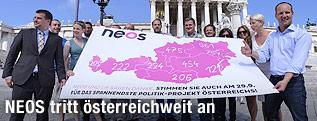 Die Spitzen der Partei NEOS mit einem Transparent der österreichweiten Unterstützungserklärungen vor dem Parlament