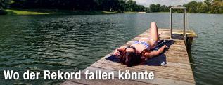 Junge Frau liegt am Steg eines Sees