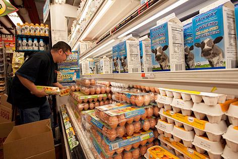 Supermarkt-Angestellter befüllt Kühlregal mit Milch und Eiern