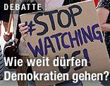 """Schild mit der Aufschrift """"Stop watching us"""""""