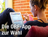 Junge Frau sieht sich auf einem iPad die ORF-Wahl-App an