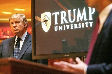 Donald Trump neben einem Bildschirm mit dem Logo der Trump University