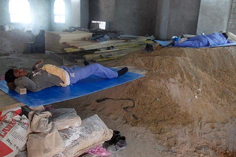 Arbeiter schlafen auf einer Baustelle