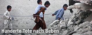Kinder gehen durch Trümmer nach einem Erdbeben