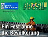 Bauarbeiter sitzt vor einem Brasilien-Poster auf dem Boden