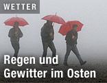 Männer gehen mit Regeschirm spazieren