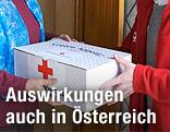 Ein Rot-Kreuz-Mitarbeiter gibt ein Essenspaket aus