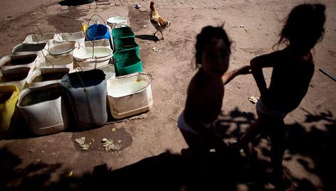 Kinder neben Plastikbehälter mit Pestizide