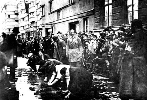 Juden, die gezwungen wurden, die Straße von politischen Parolen zu säubern