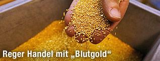 Eine Hand hält Goldgranulat