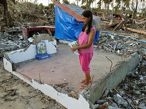 Eine Filipina steht in der Ruine ihres Hauses