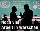 Silhouetten zweier diskutierender Teilnehmer am UNO-Weltklimagipfell in Warschau