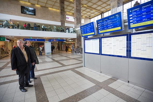 Zwei Männer stehen vor der Bahnsteiganzeige am Westbahnhof