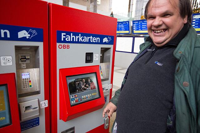 Mann steht vor einem Ticketautomaten