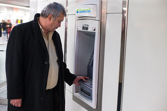 Mann steht vor einem Bankomaten