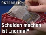 Hand greift in Geldbörse