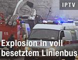 Rettungswagen und Feuerwehr beim ausgebrannten Buswrack