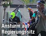 Demonstranten mit Schutzmasken vor einer Barrikade