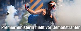 Ein Demonstrant hält sich ein Tuch vors Gesicht und wirft eine Tränengaspatrone