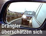Im Rückspiegel eines Auto ist knapp dahinter ein anderes Auto mit Licht zu sehen