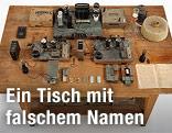 Arbeitstisch mit Paraffinblock, Geiger-Müller-Zähler, Batterien, Saugflasche und Protokollheft