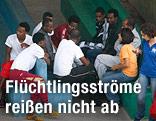 Flüchtlinge sitzen an einem Tisch