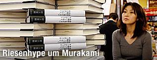 Eine Japanerin blickt auf einen Stapel Bücher des neuesten Werks von Haruki Murakami