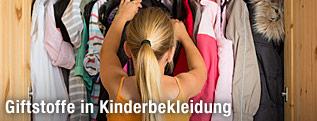 Ein Mädchen greift nach einem Kleidungsstück im Kleiderkasten