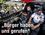Mitglieder einer Bürgerwehr halten zwei Polizisten fest