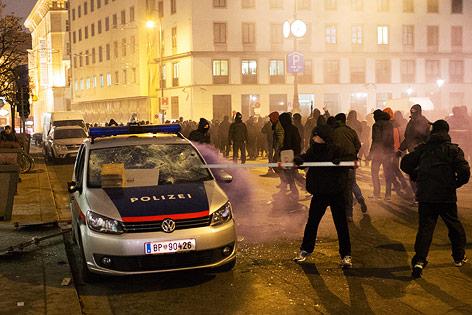 Vermummter schlägt mit einer Stange Windschutzscheibe eines Polizeiautos ein