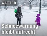 Mutter mit Kind im dichten Schneefall