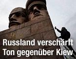 Mann besprüht russisches Monument in Kiew