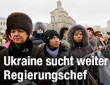 Frauen und Männer warten am Maidan-Platz